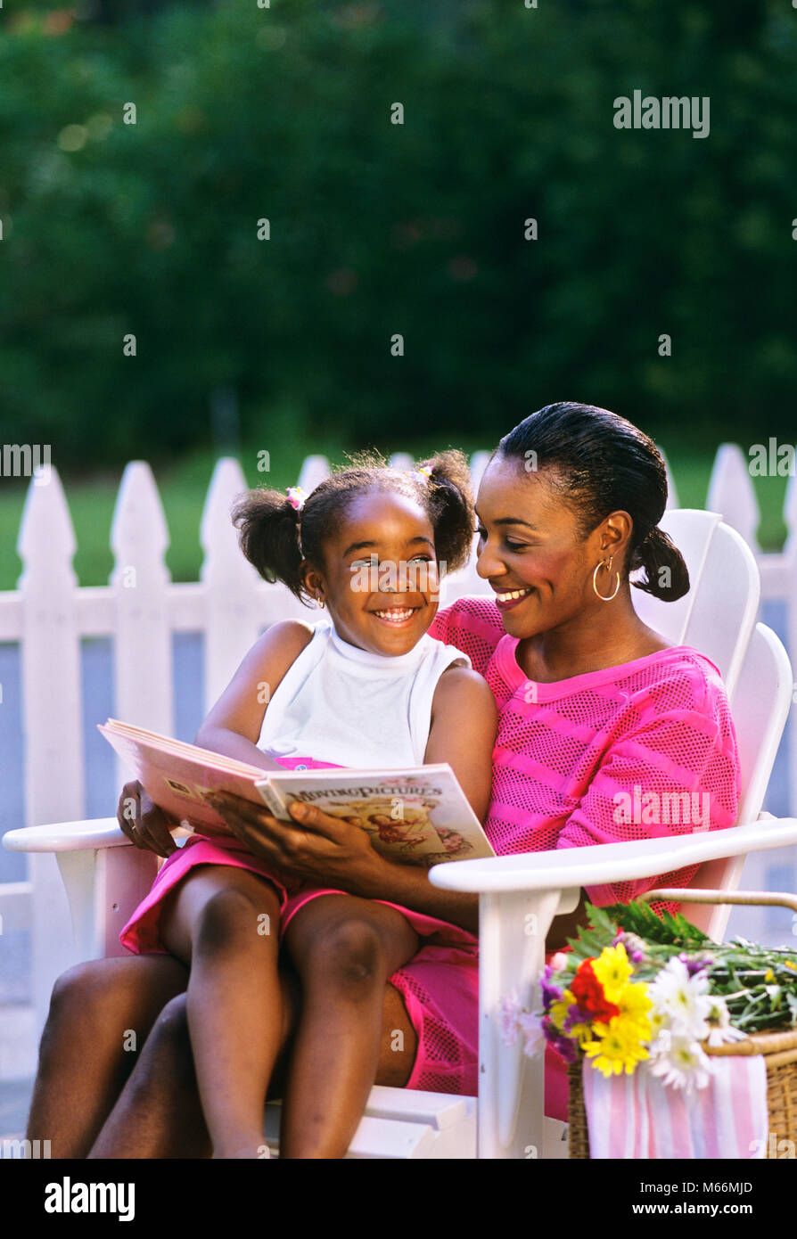 1990s MOTHER SITTING ON WHITE LAWN CHAIR WITH DAUGHTER ON HER LAP WITH BOOK - kj12900 LAF002 HARS NOSTALGIC BEAUTY - Stock Image