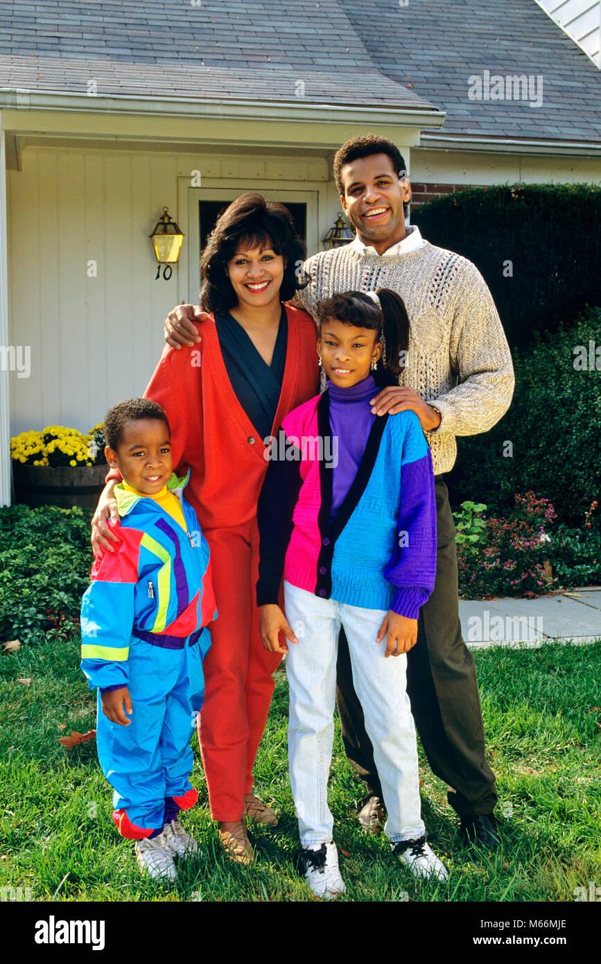 1990s AFRICAN AMERICAN FAMILY ON FRONT LAWN - kj13072 DEG002 HARS 4 COMMUNITY STYLISH SUBURBAN DIVERSITY COLOR MOTHERS - Stock Image