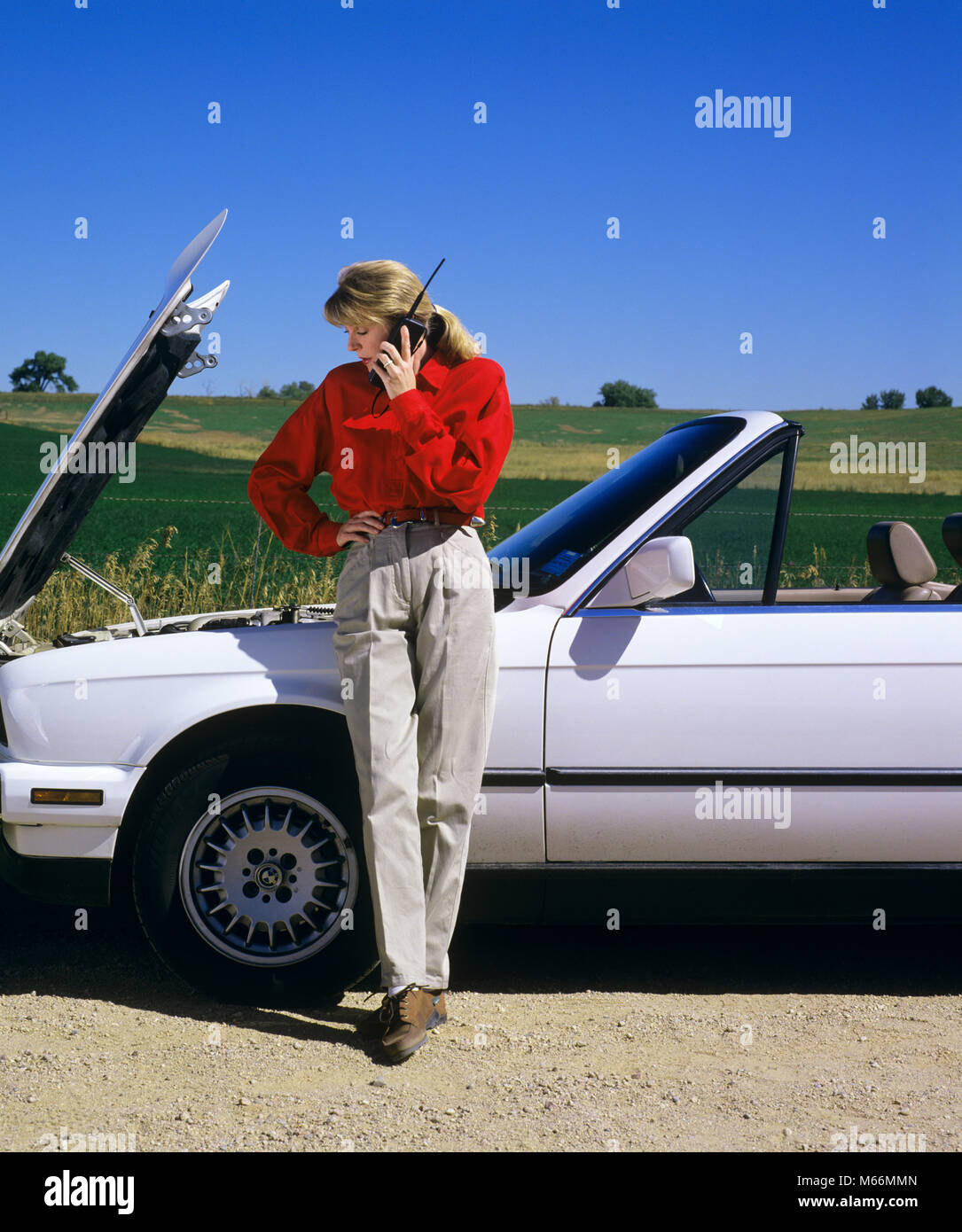 1990s WOMAN WITH CAR TROUBLE ON CELLULAR PHONE CALLING FOR ROADSIDE ASSISTANCE - km10856 DEL003 HARS FULL-LENGTH - Stock Image