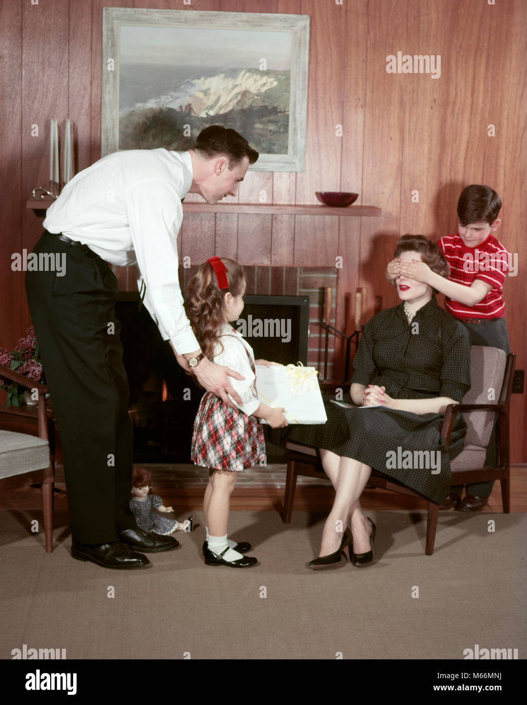 1950s FAMILY IN LIVING ROOM SURPRISING MOTHER WITH GIFT FATHER DAUGHTER HOLD GIFT SON COVERS MOMS EYES - km187 HAR001 - Stock Image