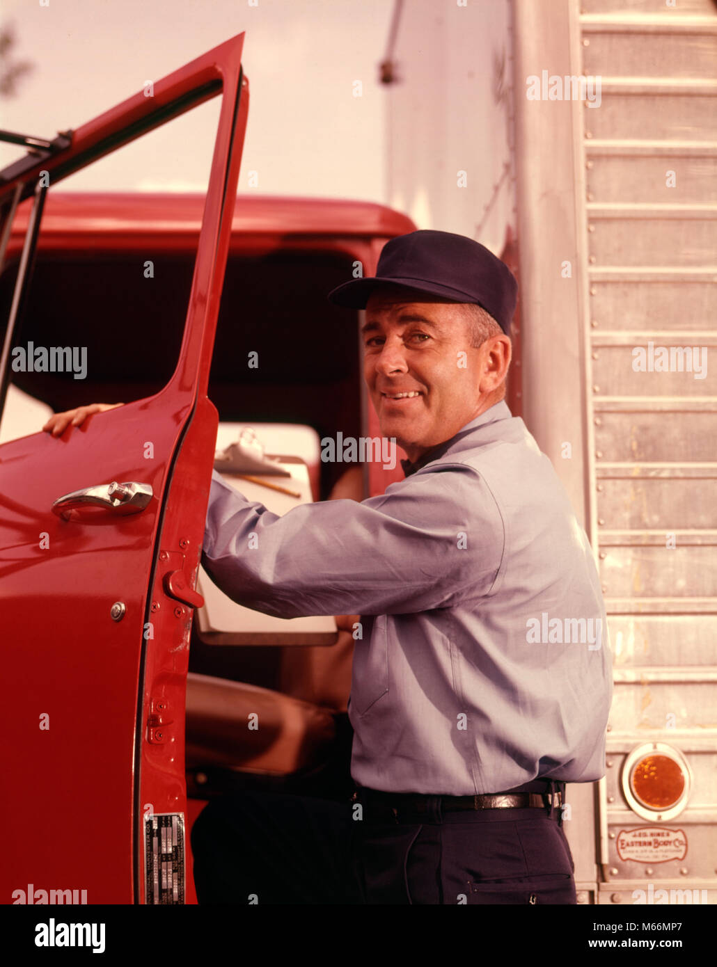 1950s 1960s SMILING MAN DELIVERY DRIVER WEARING CAP AND UNIFORM LOOKING AT CAMERA STEPPING INTO CAB THROUGH OPEN - Stock Image