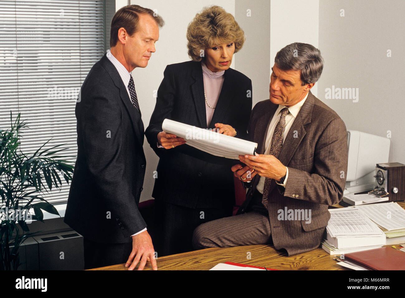 1980s 3 EXECUTIVES HOLDING MEETING IN OFFICE REVIEWING PAPER WORK SPREAD SHEET - ko2797 NET002 HARS LEADER INFORMATION - Stock Image