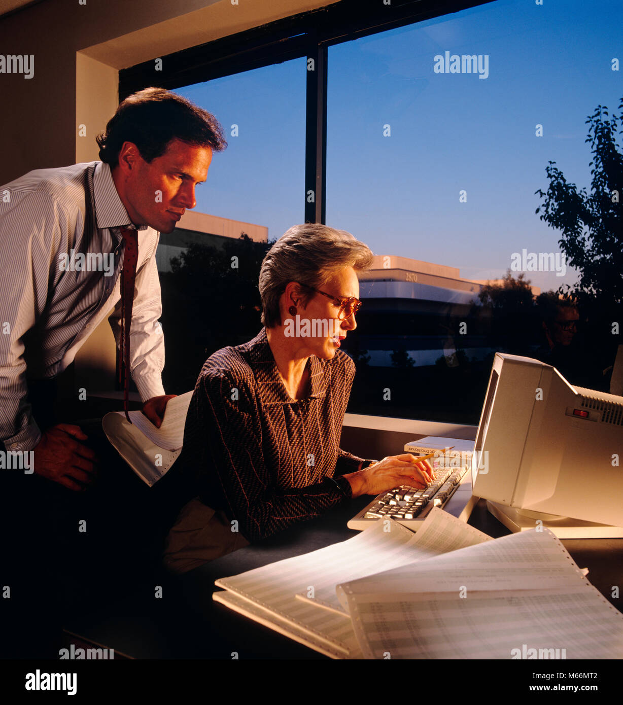 1980s 1990s MAN AND WOMAN WORKING WITH COMPUTER AT NIGHT - ko3143 KAR001 HARS CAUCASIAN LIFESTYLE FEMALES JOBS GROWNUP - Stock Image