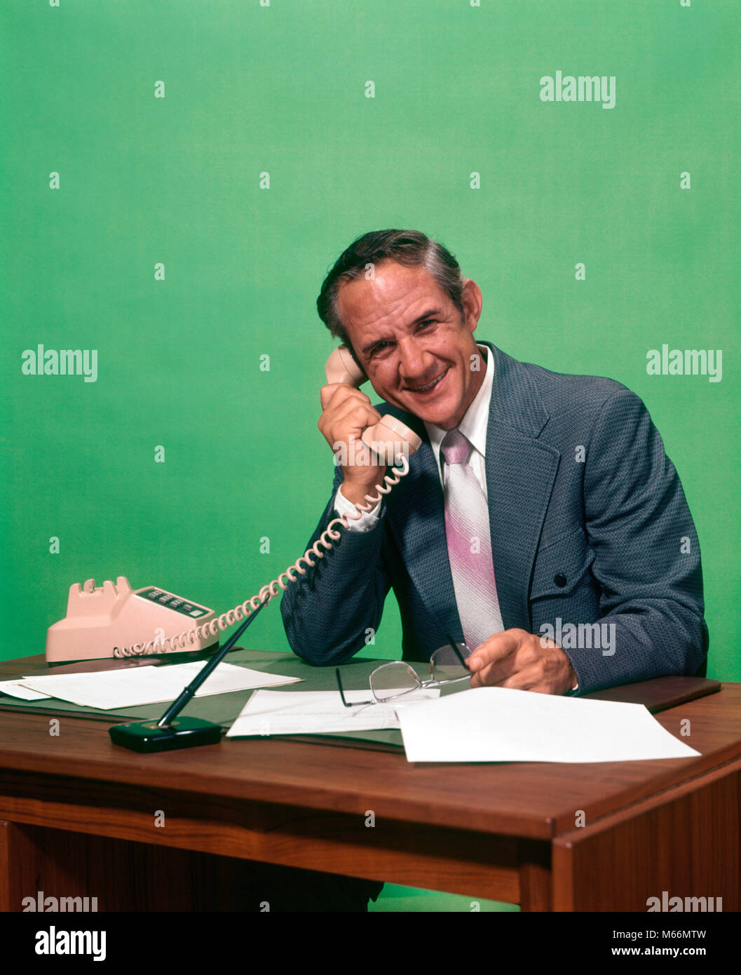 1970s SMILING MATURE MAN WEARING SUIT HOLDING GLASSES SITTING AT DESK SPEAKING ON TELEPHONE LOOKING AT CAMERA - - Stock Image