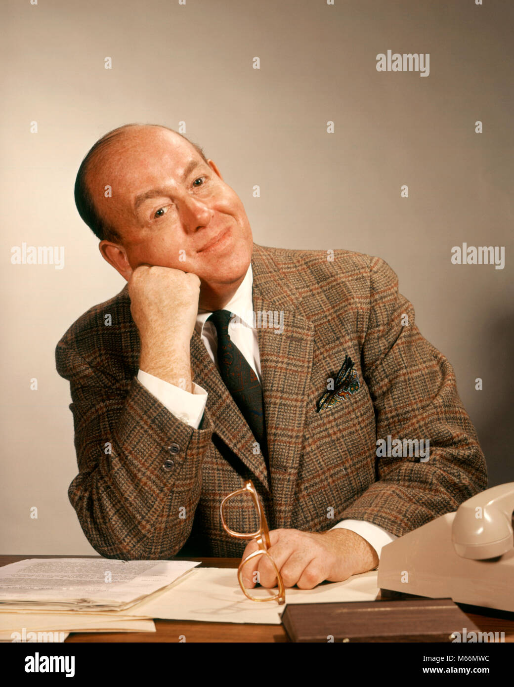 1960s BUSINESSMAN AT OFFICE DESK HAND TO FACE HEAD TILTED LEANING ON FIST LOOKING AT CAMERA - kp1310 HAR001 HARS - Stock Image
