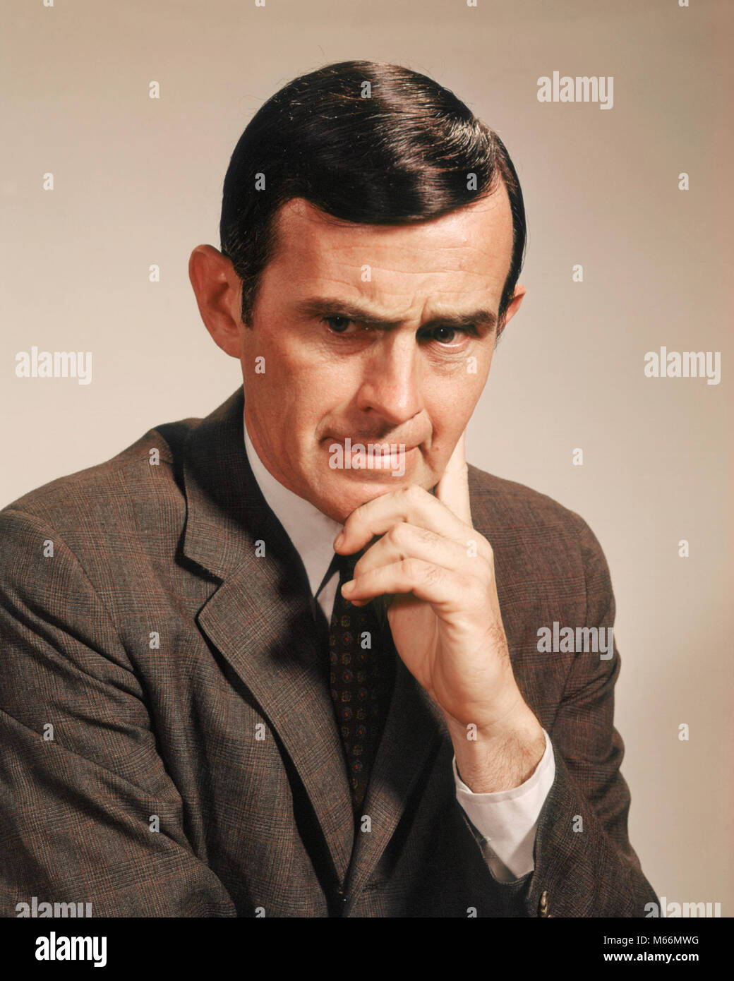 1960s PORTRAIT MAN WITH SERIOUS FACIAL EXPRESSION HAND AT CHIN HEAD DOWN LOOKING AT CAMERA - kp1371 HAR001 HARS - Stock Image