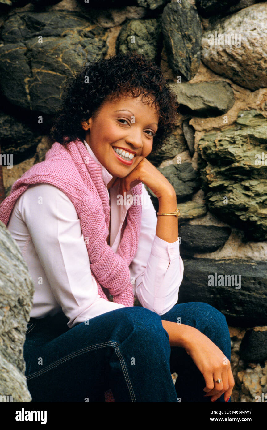 PORTRAIT OF YOUNG AFRICAN AMERICAN WOMAN LOOKING AT CAMERA SMILING WEARING PINK SWEATER OVER SHOULDERS - kp5114 - Stock Image