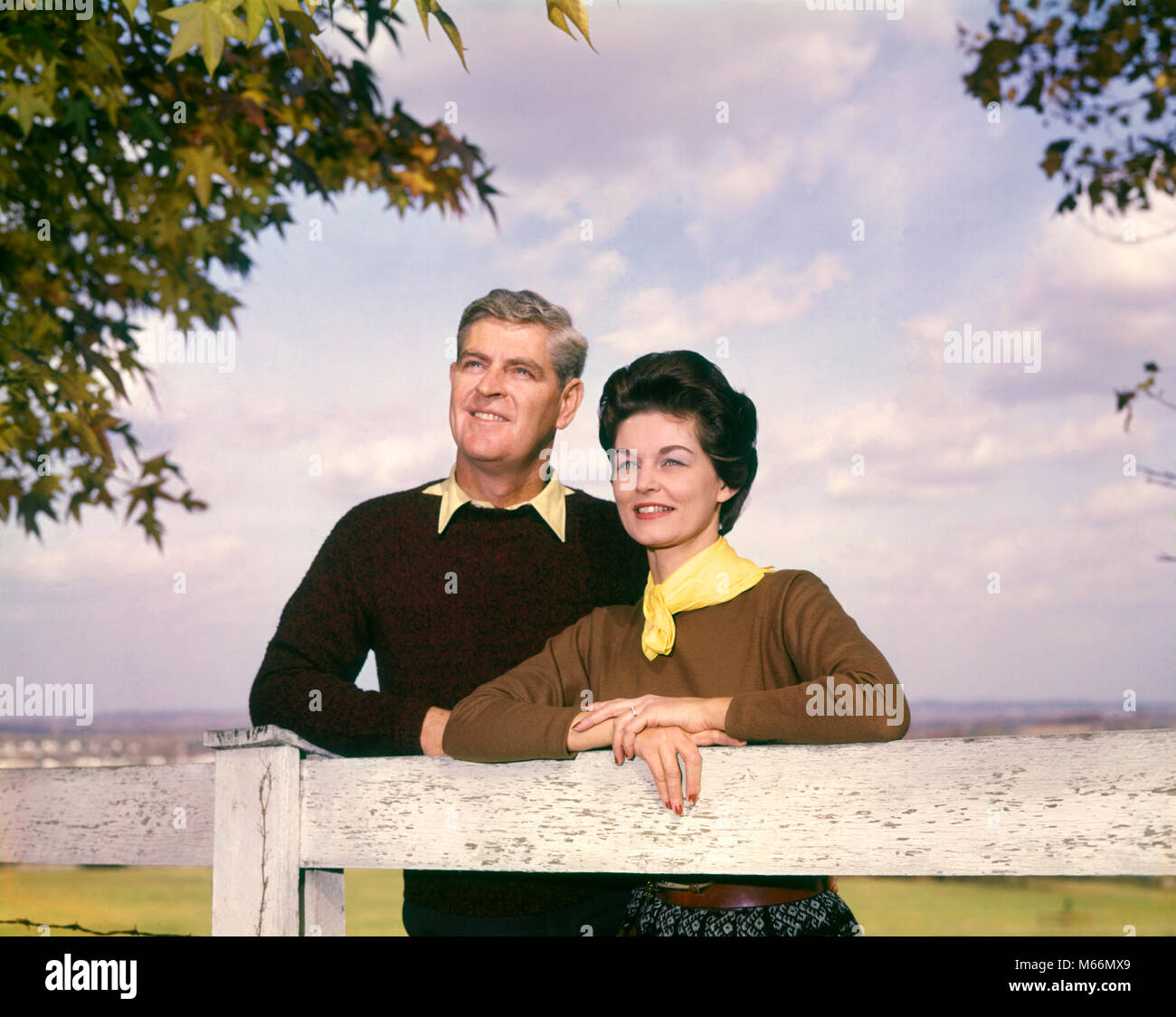 1950s 1960s SMILING MIDDLE AGE COUPLE OUTDOORS IN AUTUMN LEANING ON FENCE MAN WOMAN COUPLES MEN WOMEN - kp574 HAR001 - Stock Image