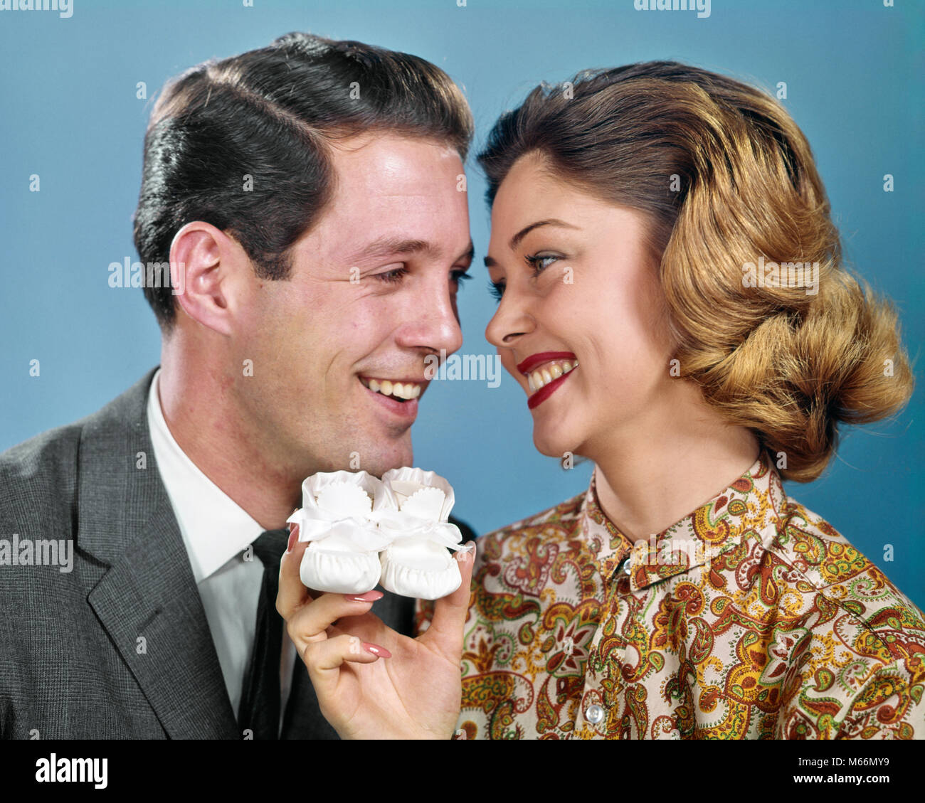1960s SMILING COUPLE HEADS TOGETHER OVER PAIR BABY BOOTIES - kp669 HAR001 HARS CELEBRATION FEMALES HEADS STUDIO - Stock Image