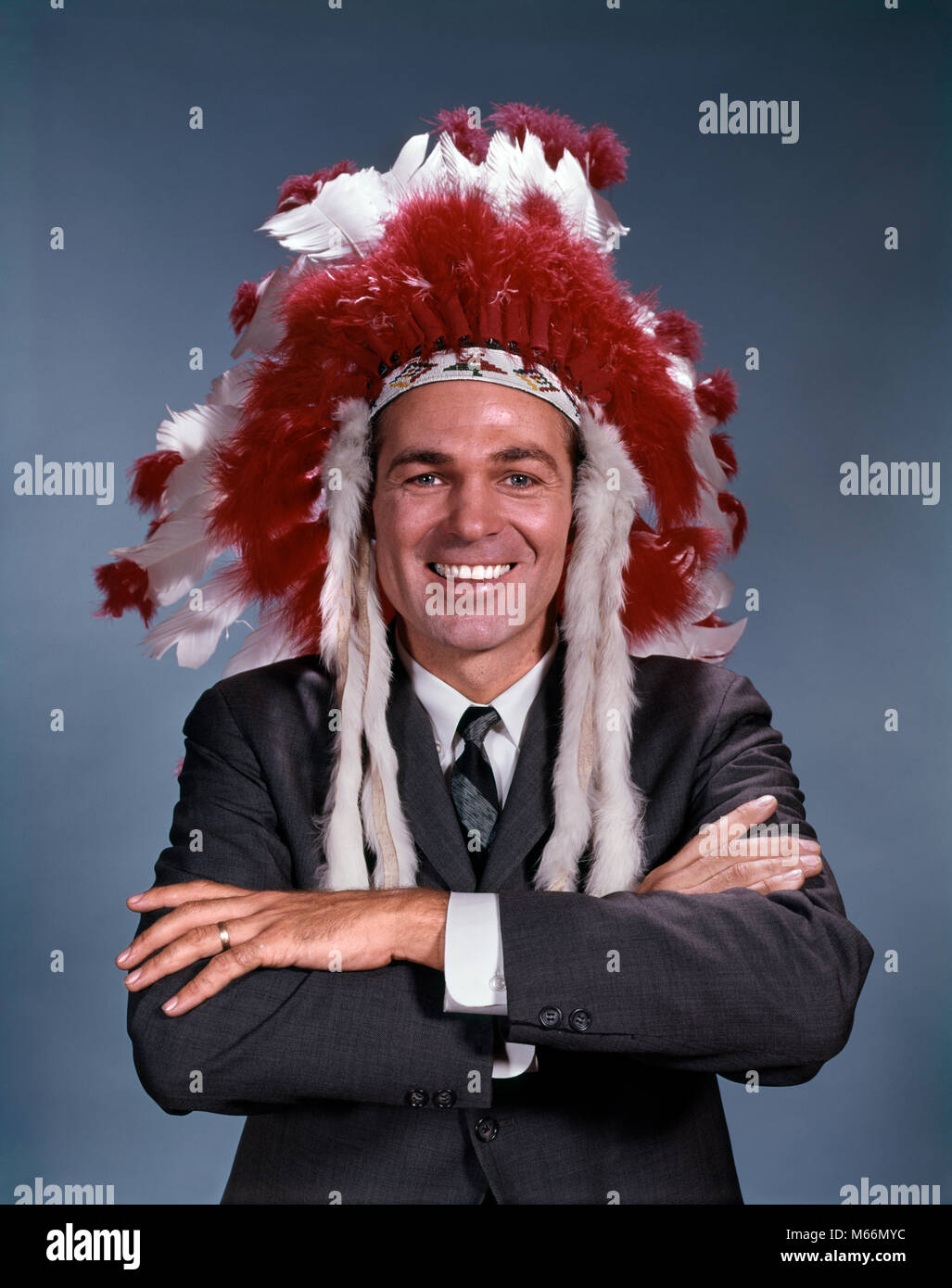 1960s SMILING MAN WEARING SUIT AND TIE AND NATIVE AMERICAN INDIAN FEATHER HEADDRESS ARMS FOLDED LOOKING AT CAMERA Stock Photo