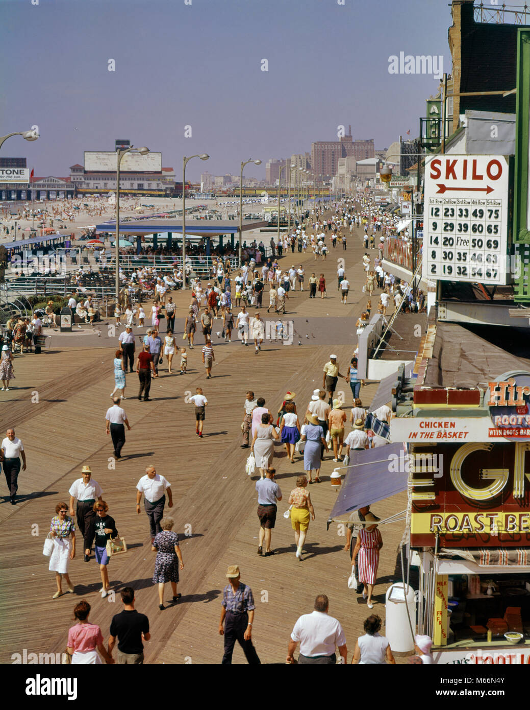 1960s FROM ABOVE LOOKING DOWN AT THE SHORE CROWD OF PEOPLE ON THE BOARDWALK OF BEACH RESORT ATLANTIC CITY NEW JERSEY - Stock Image