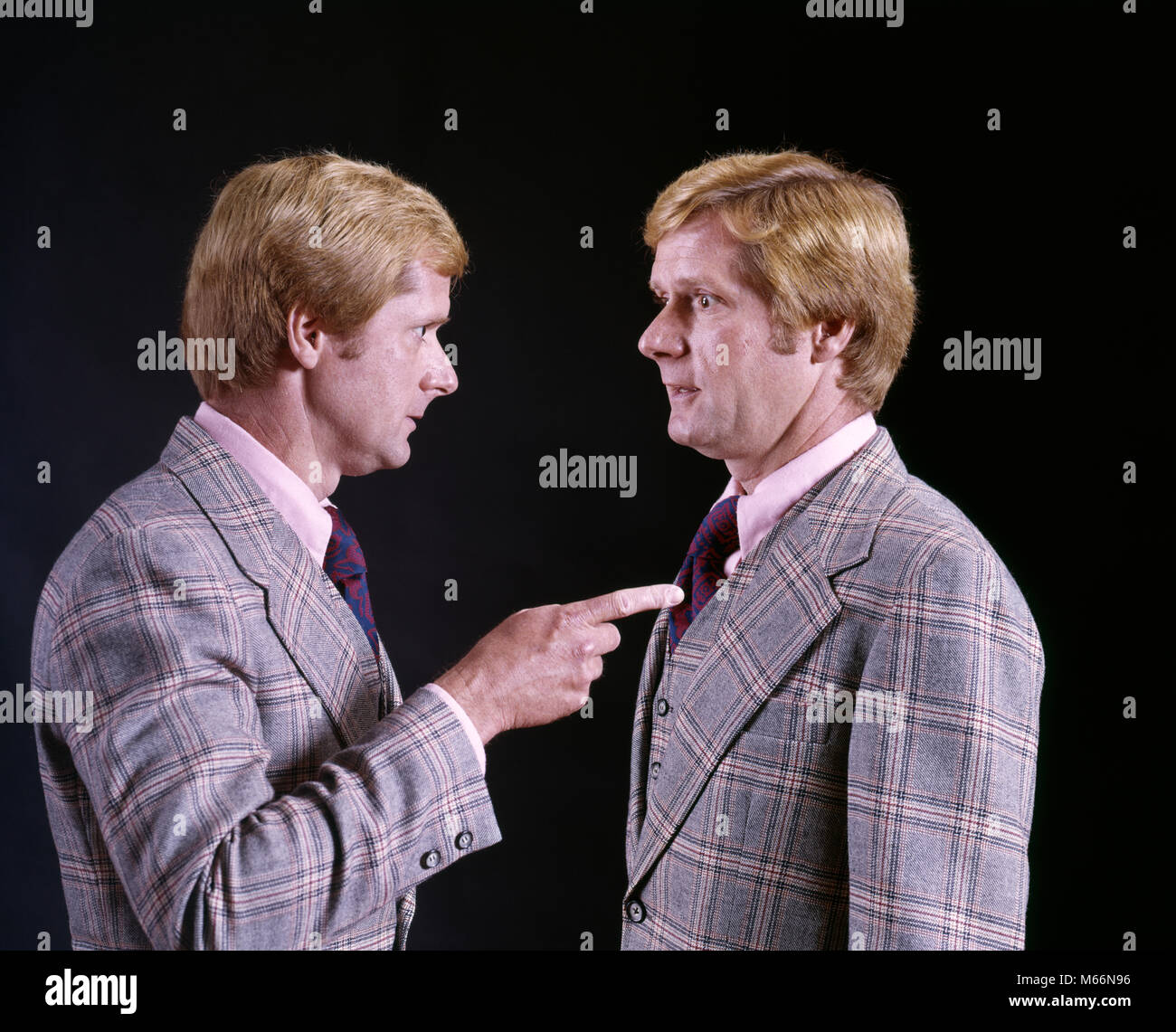 1970s BLOND MAN IN PLAID THREE PIECE SUIT POINTING ACCUSING FINGER AT HIMSELF HUMOROUS DOUBLE EXPOSURE - ks13570 - Stock Image