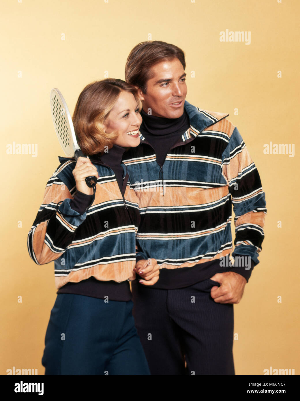 1970s SMILING COUPLE MAN WOMAN HOLDING SQUASH RACKET WEARING MATCHING STRIPED VELOUR PULLOVER SWEATERS FASHION SPORTSWEAR - Stock Image