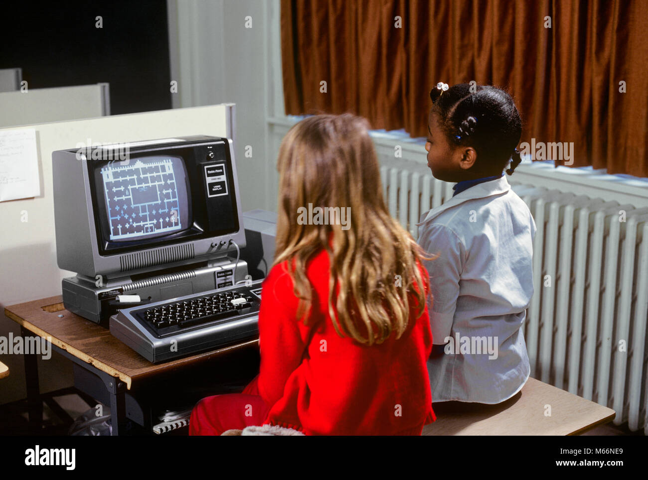1980s TWO GIRLS LEARNING ABOUT COMPUTERS BY PLAYING ON SCREEN GAME - ks22165 VAL001 HARS CONFIDENCE NOSTALGIA TOGETHERNESS - Stock Image