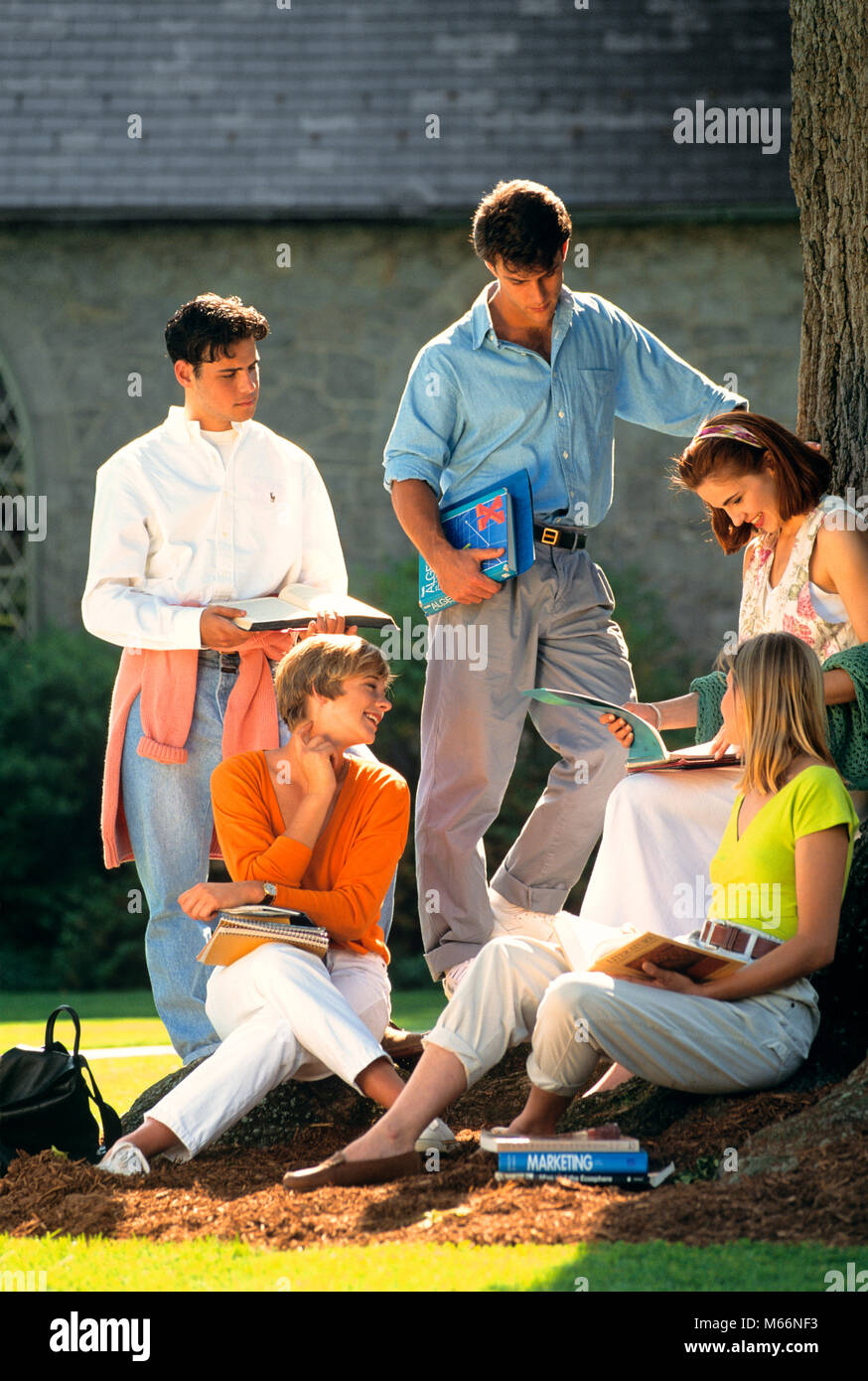 1990s FIVE COLLEGE STUDENTS WITH TEXTBOOKS ON CAMPUS TALKING UNDER A TREE - ks31723 DEG002 HARS CLOTHING NOSTALGIC Stock Photo