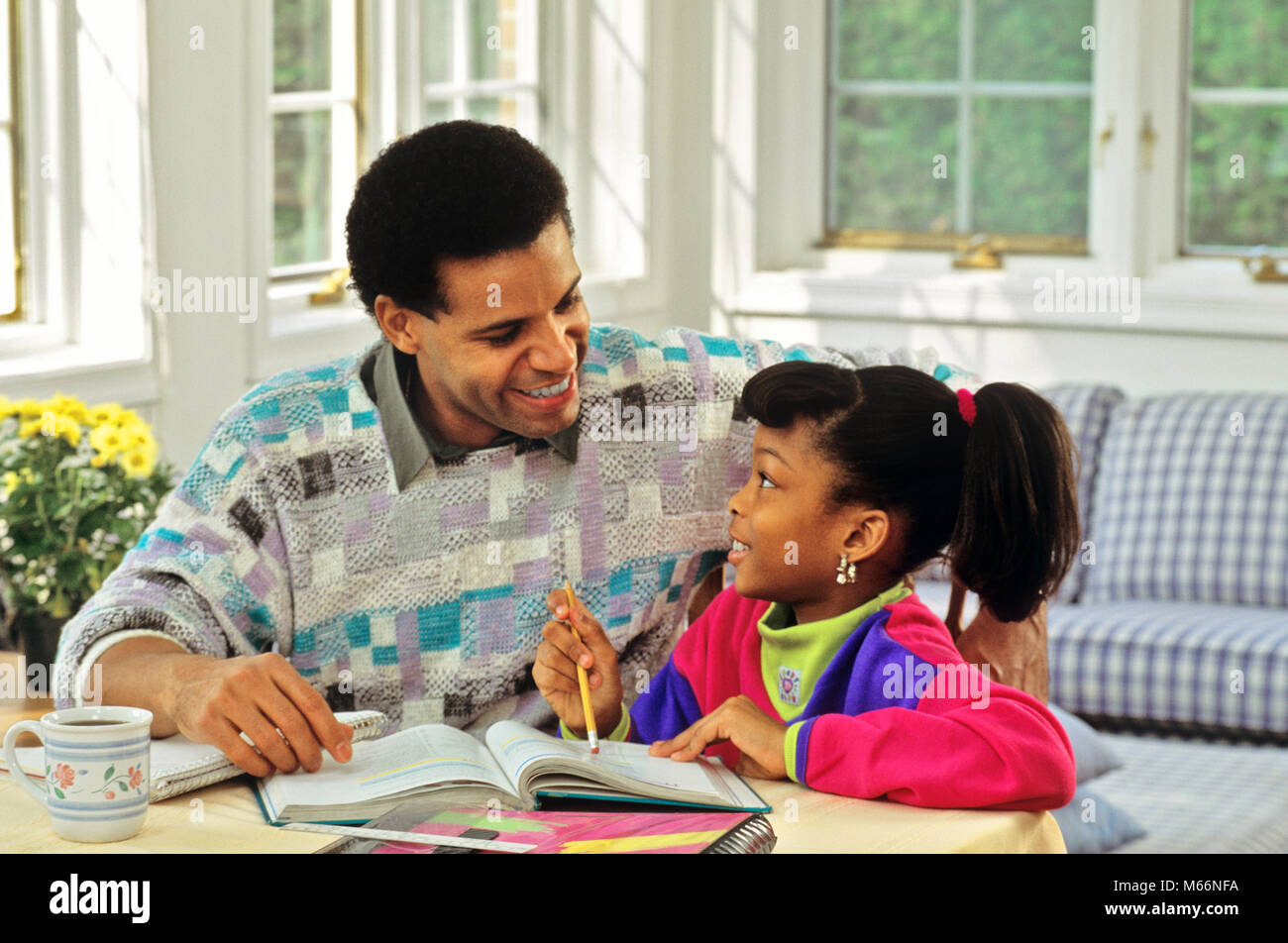 1990s AFRICAN AMERICAN FATHER HELPING DAUGHTER WITH HER HOMEWORK - ks32123 DEG002 HARS FEMALES HOME LIFE COPY SPACE - Stock Image