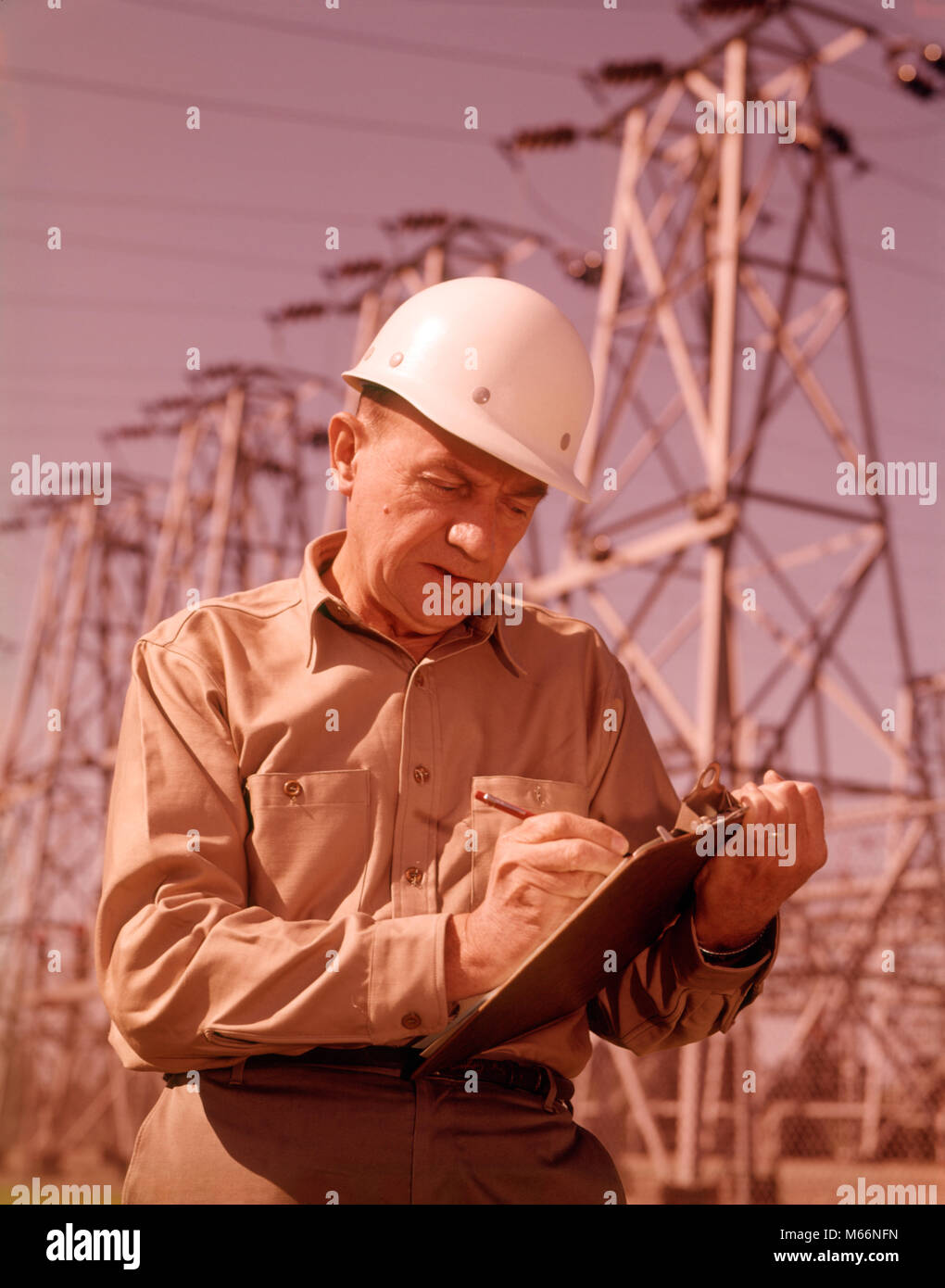 1960s MAN WORKER CLIPBOARD HARD HAT OUTDOORS BY ELECTRICAL POWER LINES - ks3412 HAR001 HARS COPY SPACE HALF-LENGTH - Stock Image