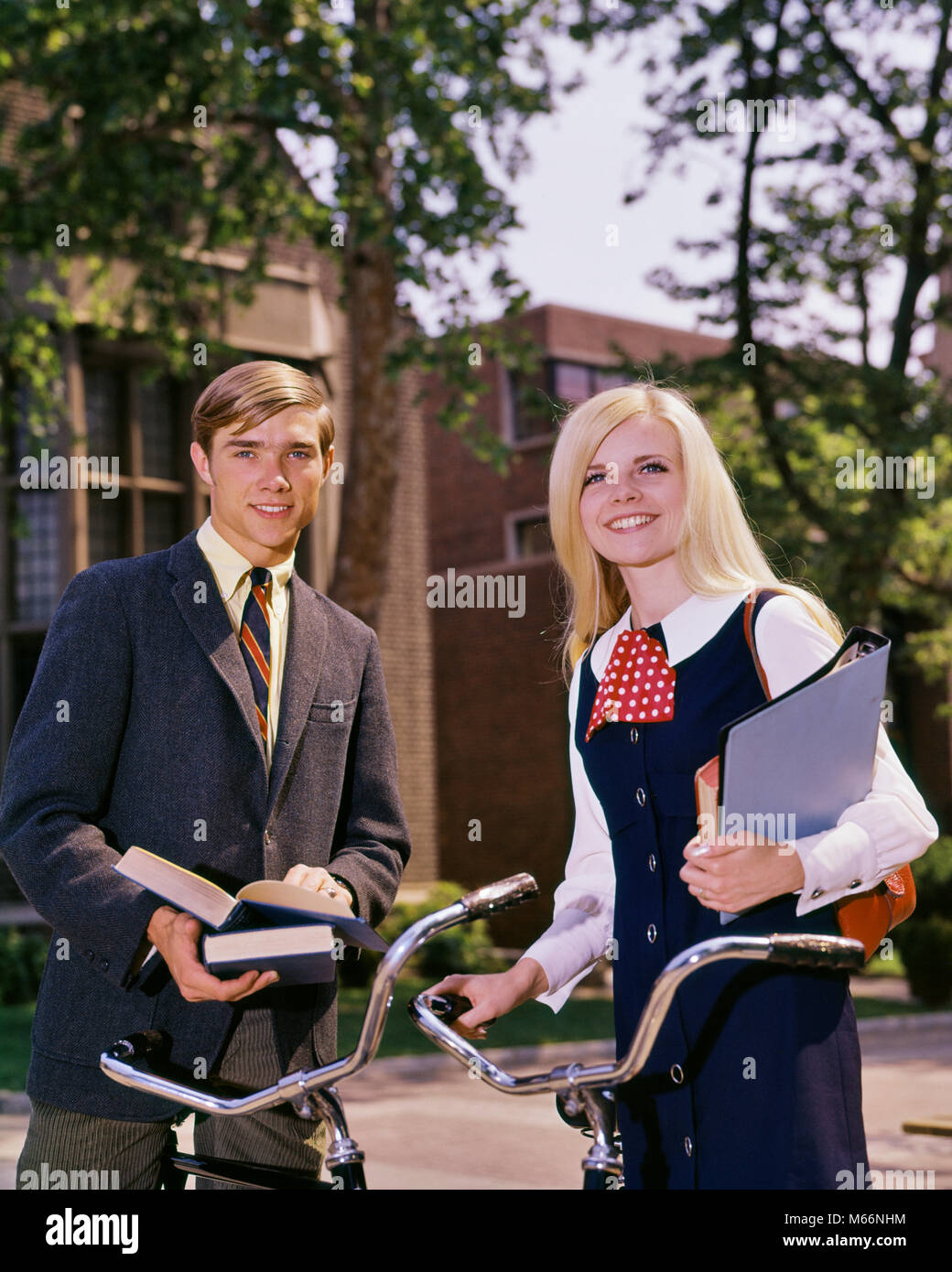 1960s PORTRAIT STUDENT COUPLE ON CAMPUS WITH BIKES AND BOOKS LOOKING AT CAMERA - ks5841 HAR001 HARS JOY LIFESTYLE - Stock Image