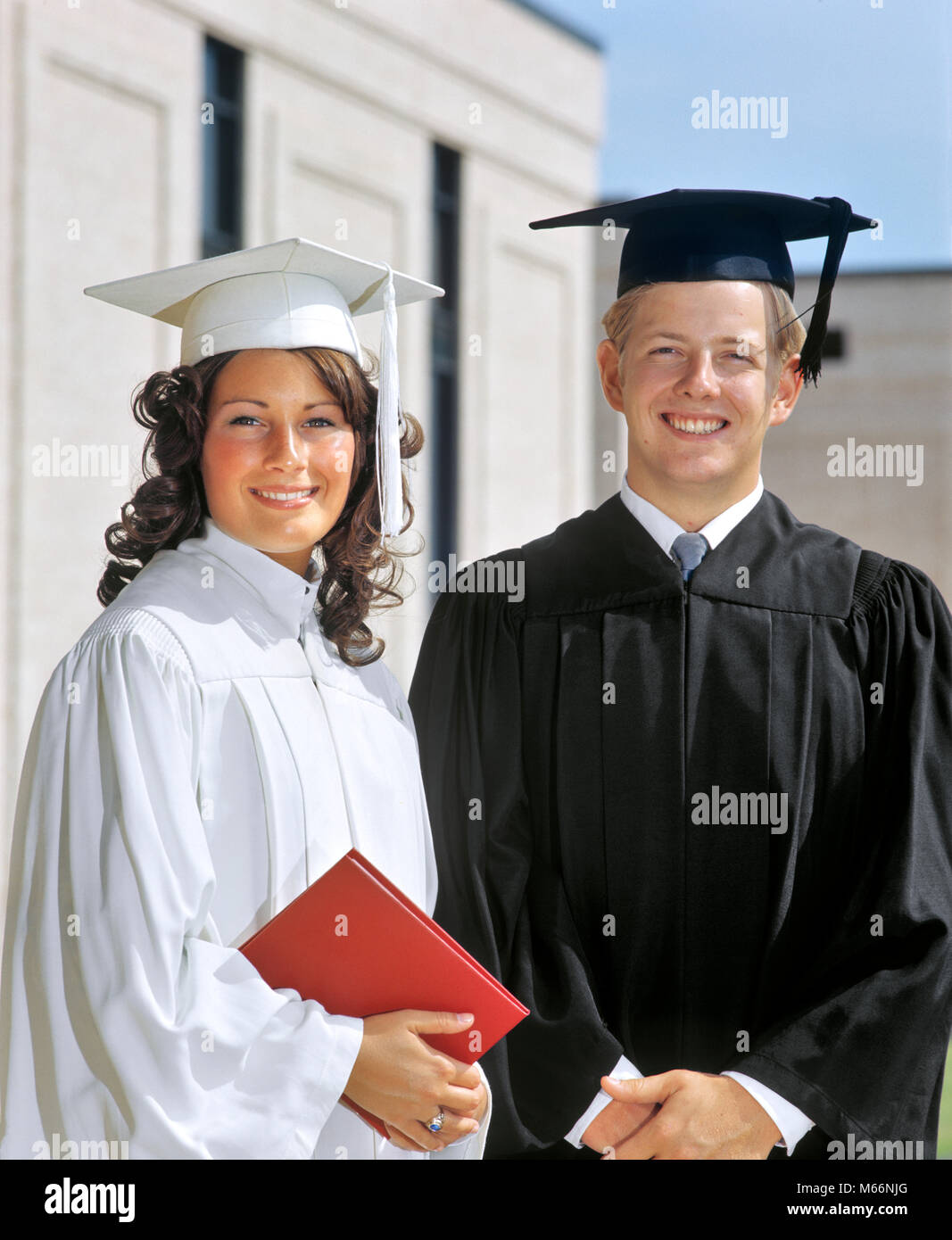 1970s PORTRAIT STUDENT COUPLE IN GRADUATION ROBES LOOKING AT CAMERA - ks9467 HAR001 HARS CELEBRATION FEMALES COPY - Stock Image