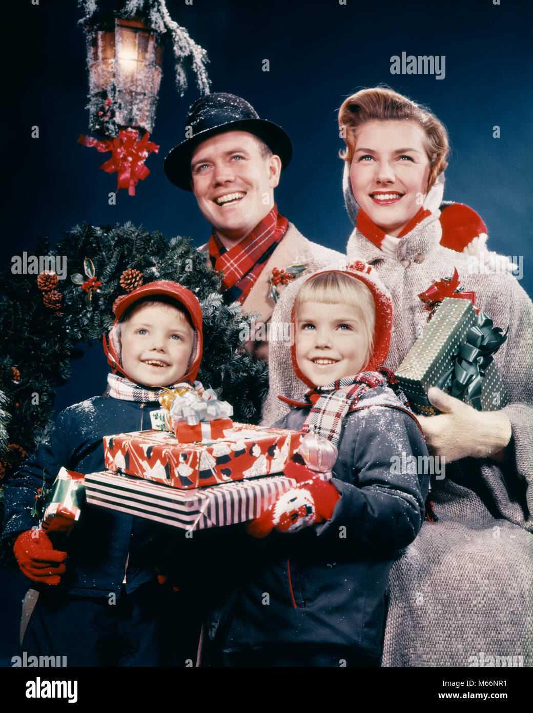 1950s FAMILY MAN WOMAN TWO KIDS HOLDING CHRISTMAS PRESENTS SMILING STANDING BENEATH LANTERN - kx2215 HAR001 HARS - Stock Image