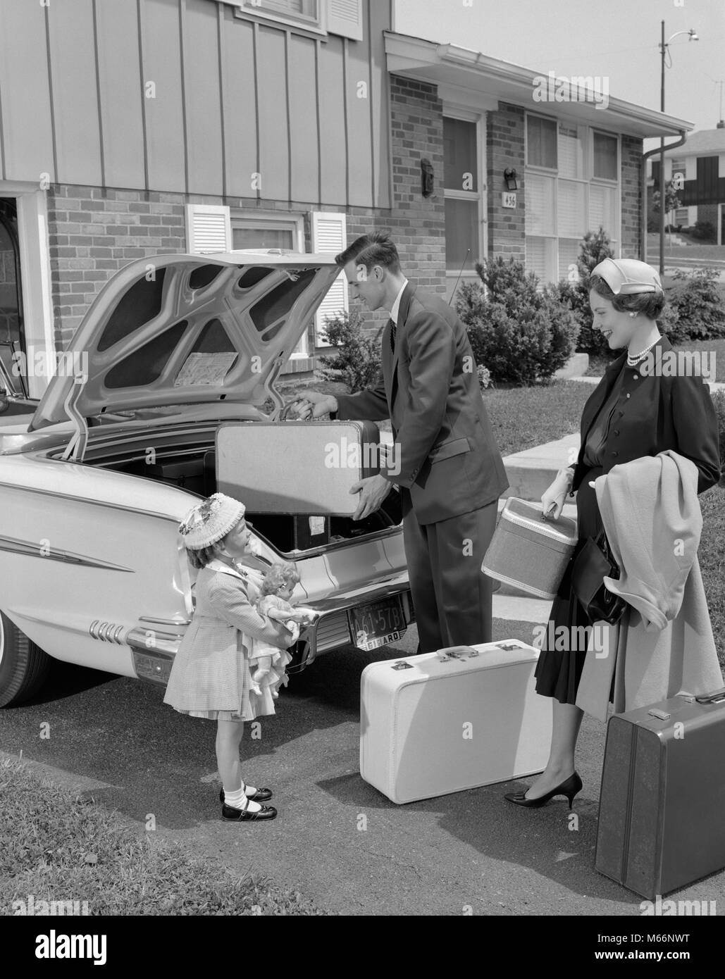 1950s FAMILY PACKING LUGGAGE INTO CAR TRUNK - m1108 HAR001 HARS STYLISH SUBURBAN PACKING RELATIONSHIP MOTHERS GROUPS - Stock Image