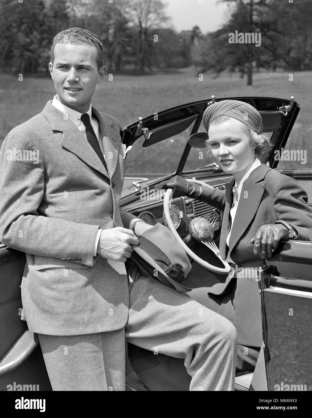 1930s COUPLE WOMAN SITTING IN DRIVER'S SEAT OF CONVERTIBLE CAR MAN LEANING ON OPEN DOOR HOLDING HAT - m161 HAR001 - Stock Image
