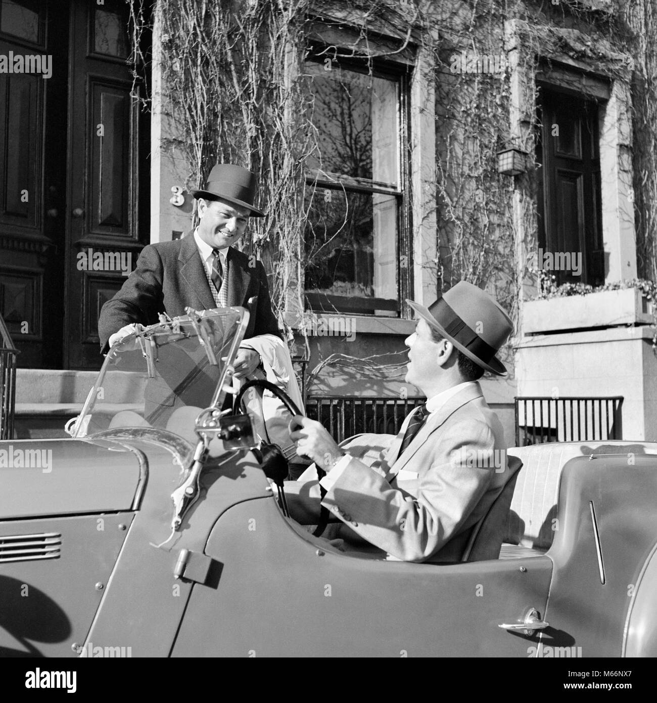 1950s 1960s TWO BUSINESSMEN TALKING ON STREET ONE SITTING IN SPORTS CAR CONVERTIBLE TWO SEATER - m2226 CRR001 HARS - Stock Image