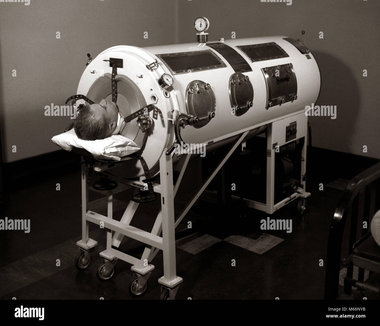 1930s 1940s 1950s MAN LYING IN IRON LUNG NEGATIVE PRESSURE VENTILATOR ARTIFICIAL BREATHING MACHINE - m6512 HAR001 - Stock Image