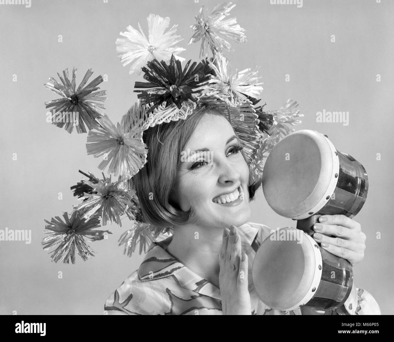 1960s SMILING WOMAN WAEARING GOOFY STRAW HAT PLAYING BONGO DRUMS - m7415 HAR001 HARS LADIES DRUMS CARIBBEAN INDOORS - Stock Image