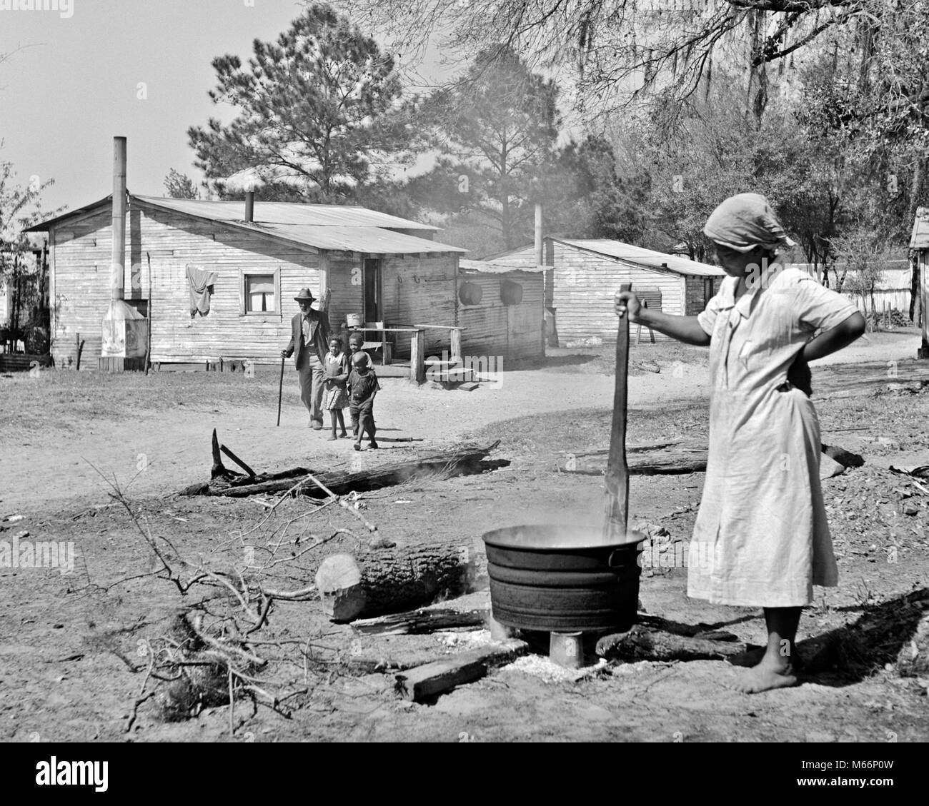 1930s ELDERLY MAN AND GRANDCHILDREN WALKING BY AFRICAN AMERICAN WOMAN STIRRING CALDRON ON OPEN FIRE ON TURPENTINE - Stock Image