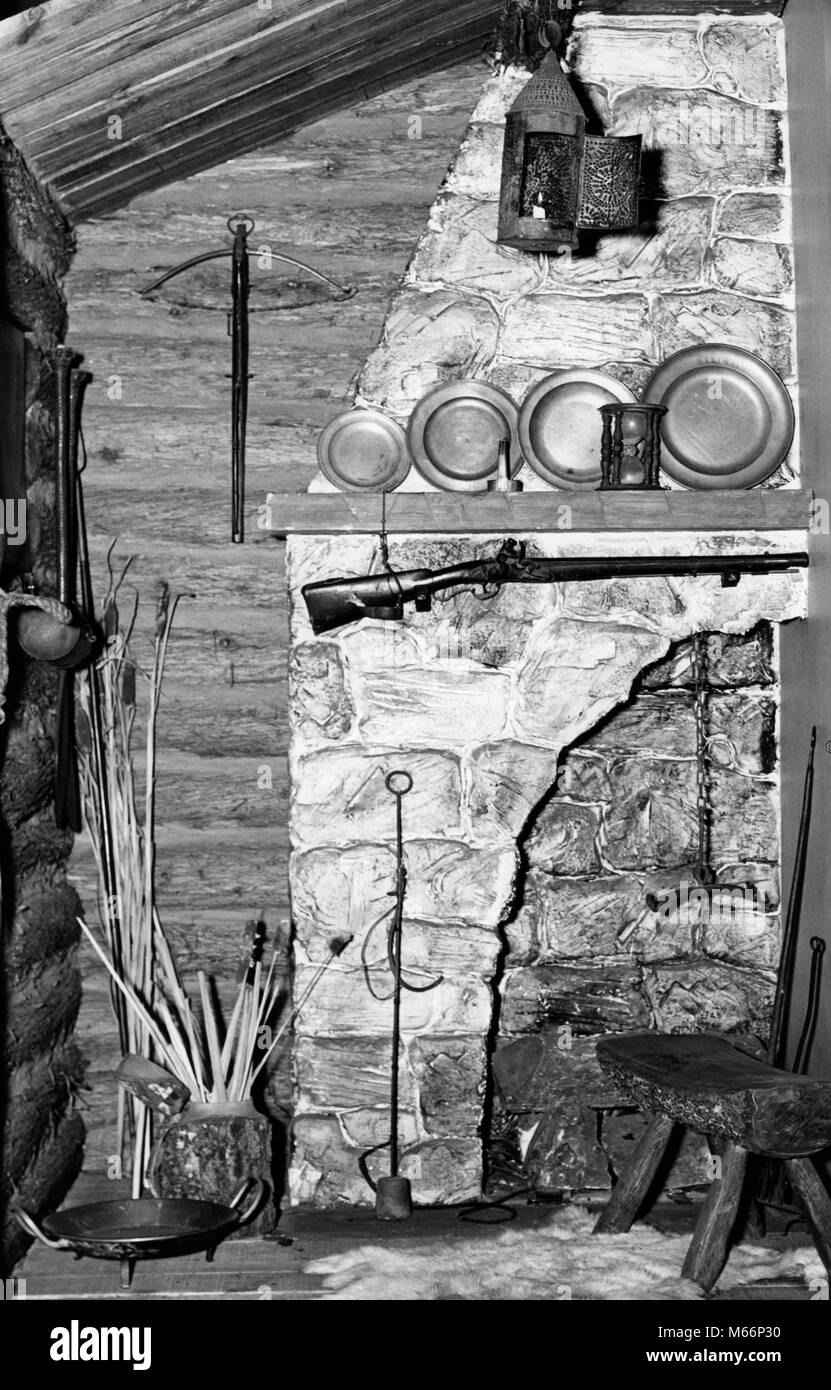 1600s 1620 CORNER OF EARLY AMERICAN COLONIAL LOG CABIN STONE FIREPLACE MANTEL GUN PEWTER PLATES PIERCED TIN CANDLE - Stock Image