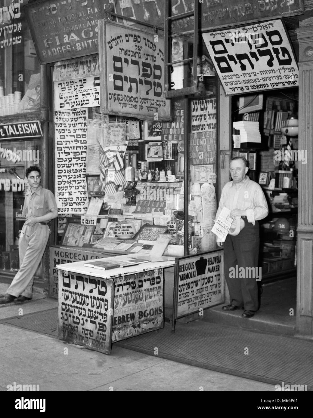 1940s LOWER EAST SIDE SHOP SIGN FOR FLAGS BOOKS BADGES BUTTON IN YIDDISH HEBREW ALPHABET MANHATTAN NEW YORK CITY - Stock Image