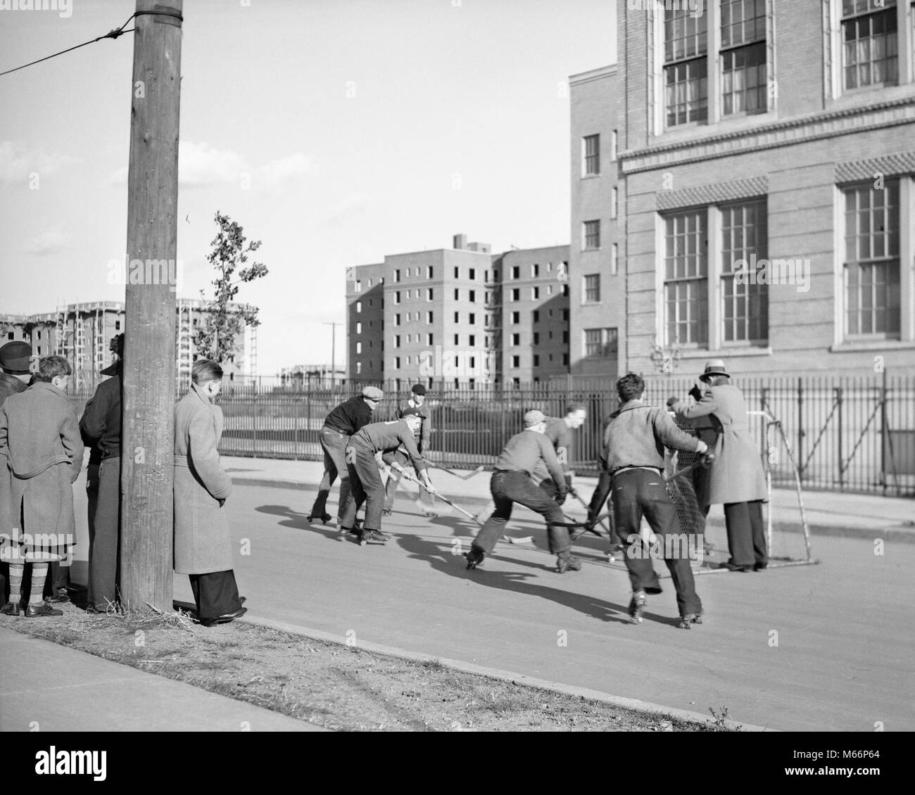 1930s GROUP TEEN BOYS PLAYING STREET HOCKEY IN BOROUGH OF QUEENS NEW YORK CITY USA - q44831 CPC001 HARS FULL-LENGTH - Stock Image