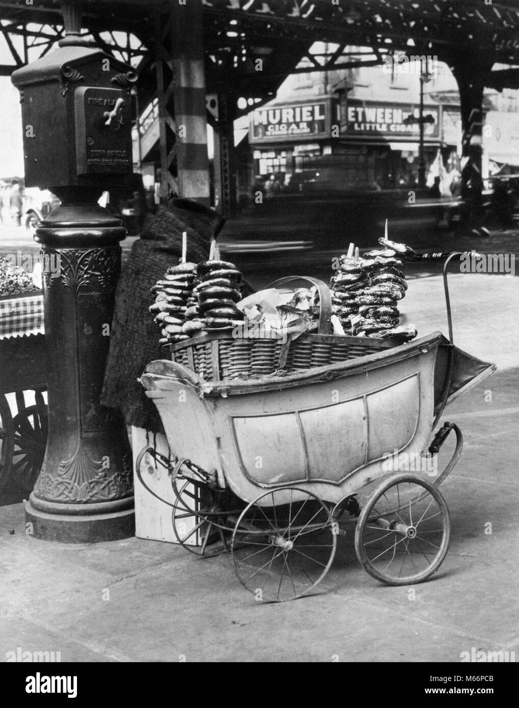 1930s DEPRESSION SCENE OF PRETZEL VENDOR CART MADE FROM A BABY CARRIAGE NEXT TO FIRE ALARM BOX NEW YORK CITY USA - Stock Image