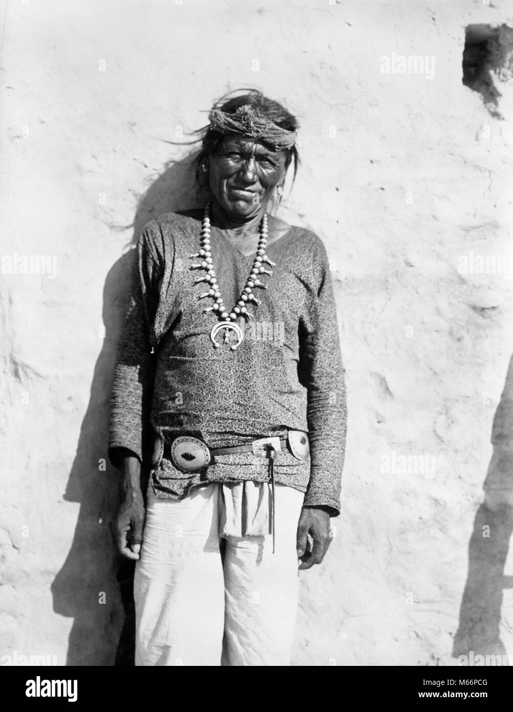 1890 1890s PORTRAIT NATIVE AMERICAN HOPI INDIAN MAN SMILING WEARING SQUASH BLOSSOM NECKLACE LOOKING AT CAMERA - - Stock Image