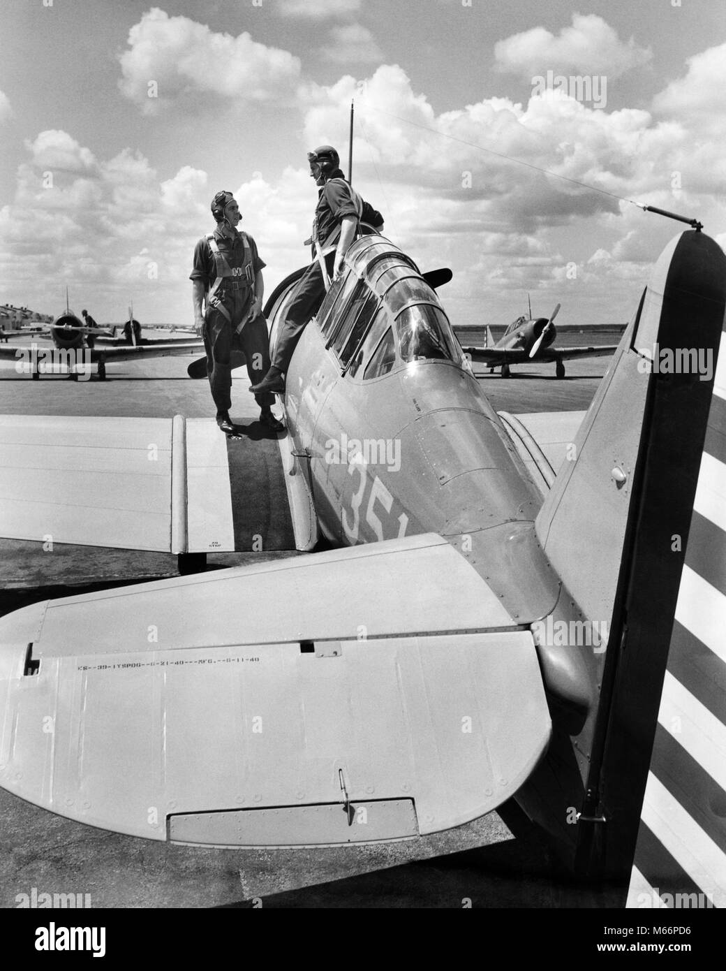 1940s 2 ARMY PILOTS STANDING FUSELAGE OF SLIDING COCKPIT SINGLE ENGINE AIRPLANE WING US ARMY AIR CORPS RANDOLPH - Stock Image