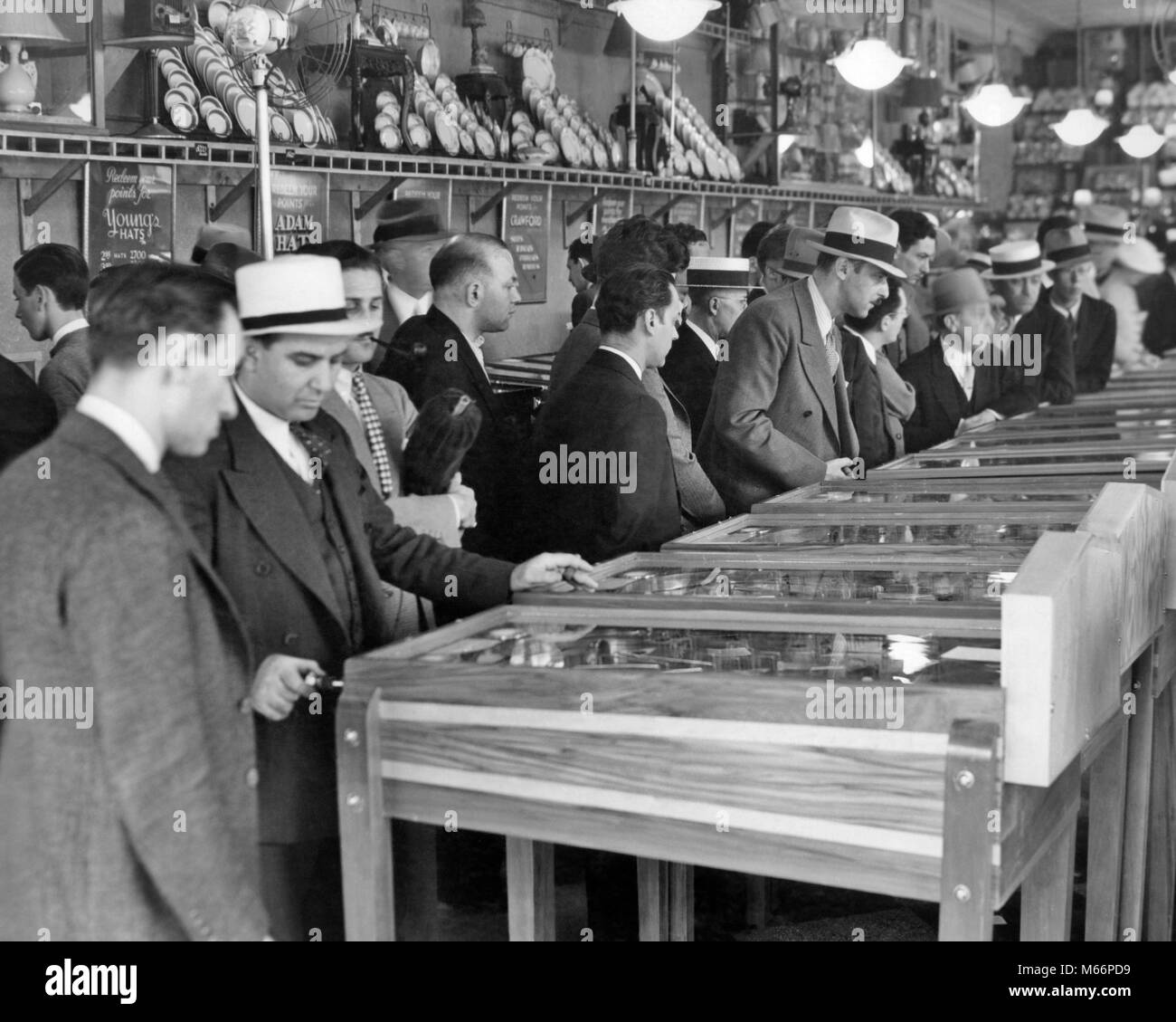 1930s GROUP MEN WEARING HATS PLAYING MARBLE PINBALL MACHINES IN BROADWAY AMUSEMENT ARCADE TIMES SQUARE NEW YORK - Stock Image