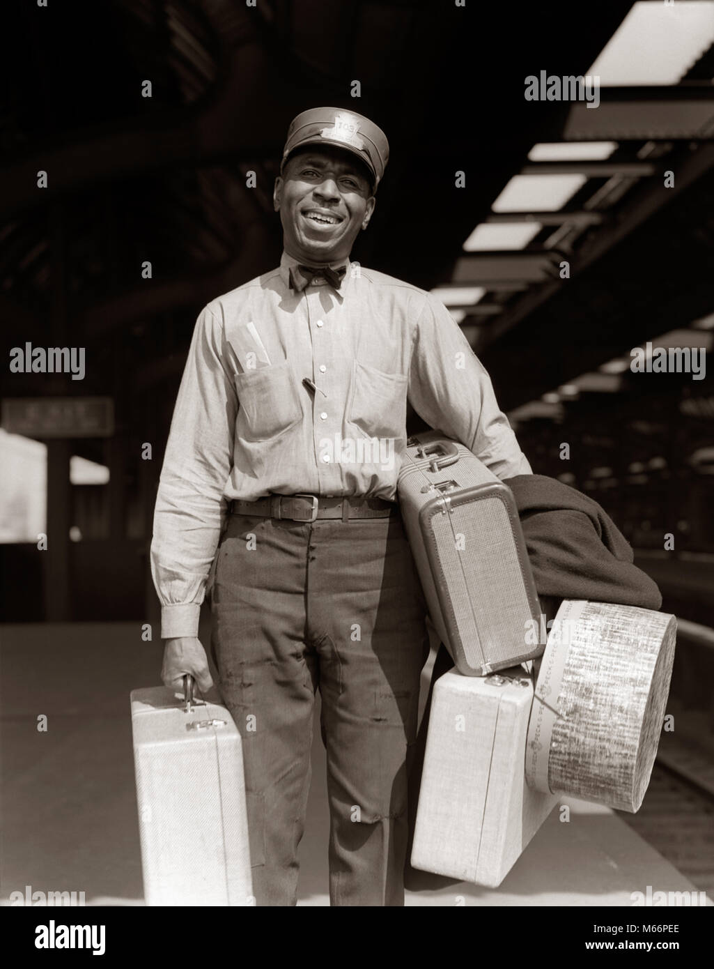 1930s 1940s SMILING AFRICAN AMERICAN MAN RAILROAD PASSENGER TRAIN RED CAP PORTER CARRYING LUGGAGE & SUITCASES - Stock Image