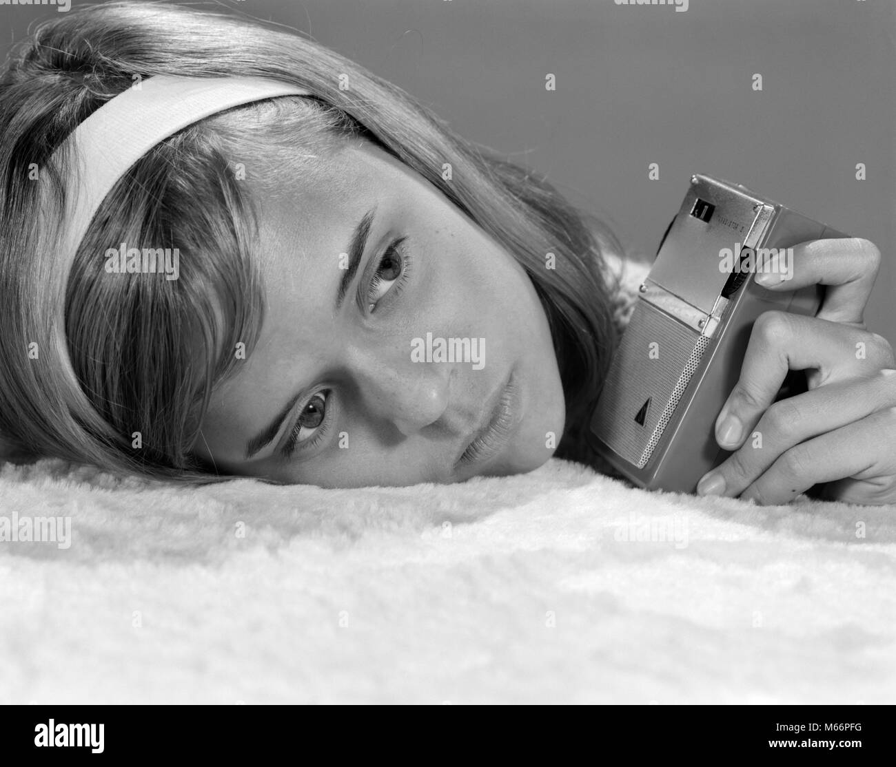 1950s 1960s CLOSE-UP OF TEENAGE GIRL WITH HEAD ON PILLOW LISTENING TO HAND-HELD TRANSISTOR RADIO - r19123 HAR001 - Stock Image