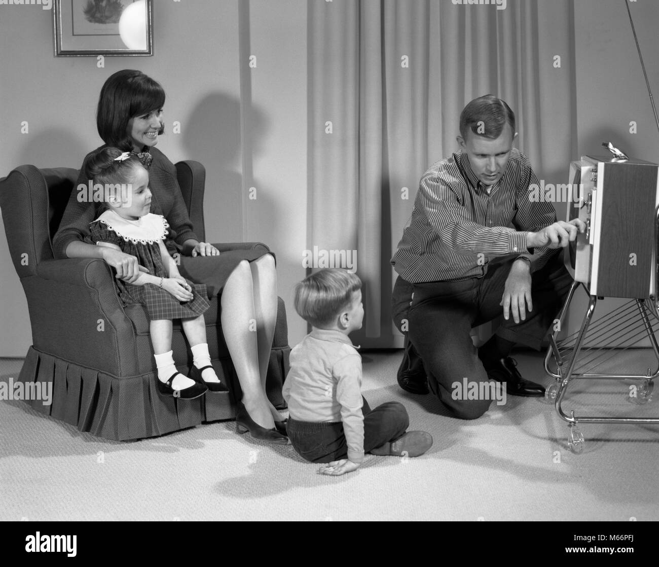 1960s FAMILY OF FOUR WATCHING PORTABLE TELEVISION MOTHER