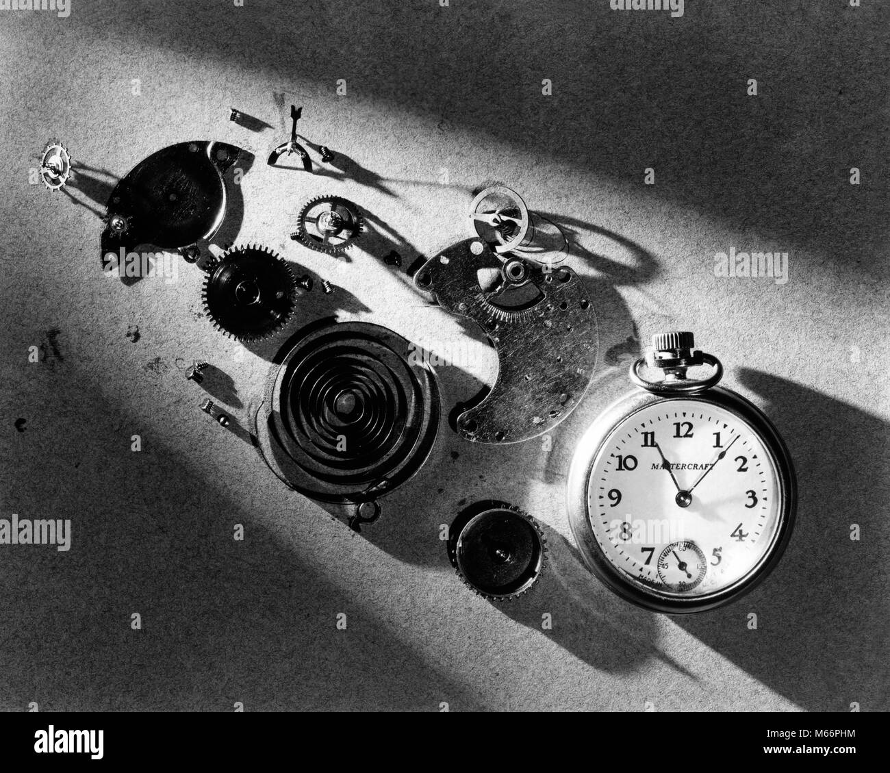 1940s POCKET WATCH AND PARTS SPRINGS GEARS MECHANISM IN DRAMATIC LIGHT - s10161 HAR001 HARS TIMEPIECE - Stock Image
