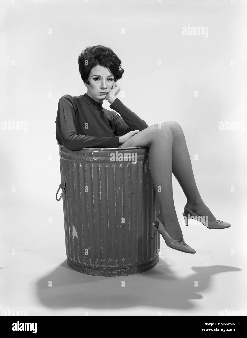 1960s UNHAPPY SAD DEPRESSED WOMAN IN TRASH CAN WEARING HIGH HEELS LOOKING AT CAMERA