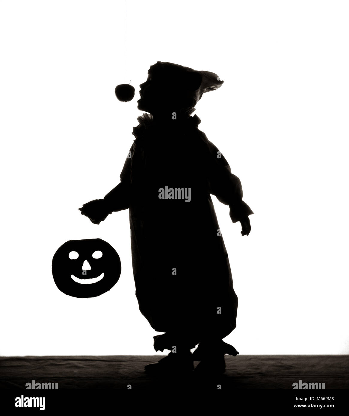 1950s HALLOWEEN SILHOUETTED CHILD IN COSTUME JACK-O-LANTERN CANDIED APPLE ON STRING - s1769 HAR001 HARS OLD FASHIONED - Stock Image