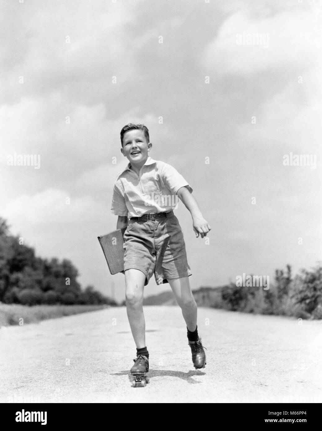 1930s 1930s SMILING BOY ROLLER SKATING TO SCHOOL LOOKING AT CAMERA CARRYING TEXTBOOK BINDER - s780 HAR001 HARS COPY - Stock Image