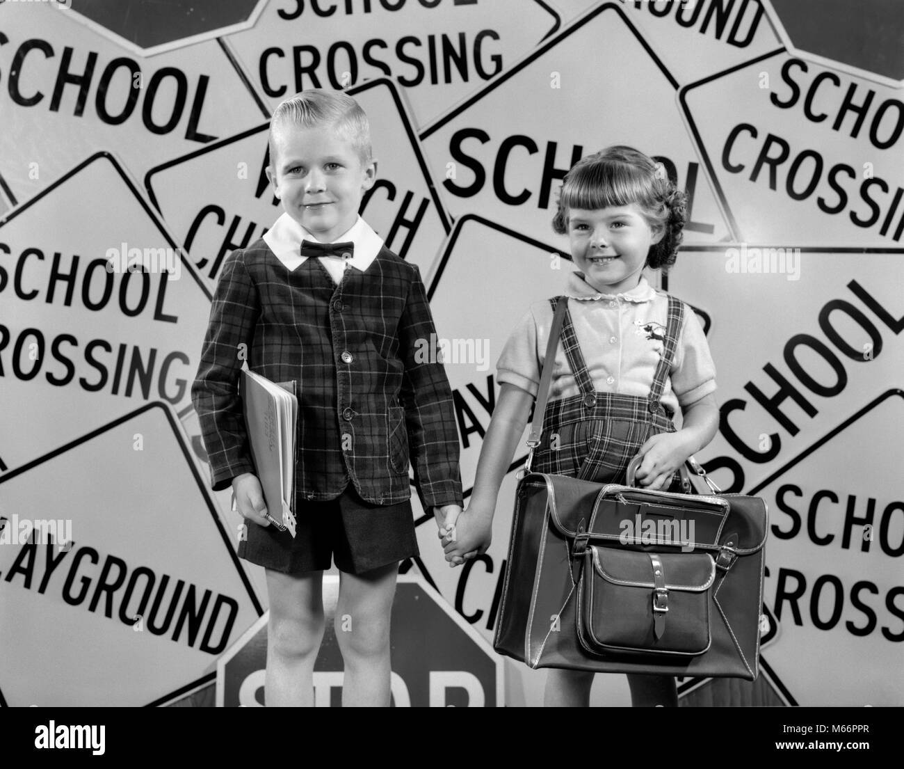 1950s MONTAGE OF BOY & GIRL IN PLAID JACKET & SKIRT HOLDING HANDS LOOKING AT CAMERA SUPERIMPOSED OVER SCHOOL - Stock Image