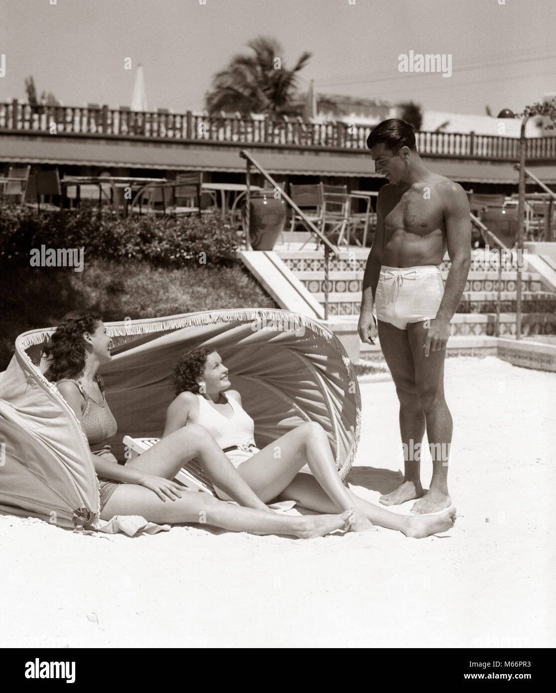 3c45393e05db3 1930s 1940s MAN BATHING TRUNKS TALKING TO TWO WOMEN LAYING UNDER HOTEL  CANVAS SUN SCREEN TROPICAL
