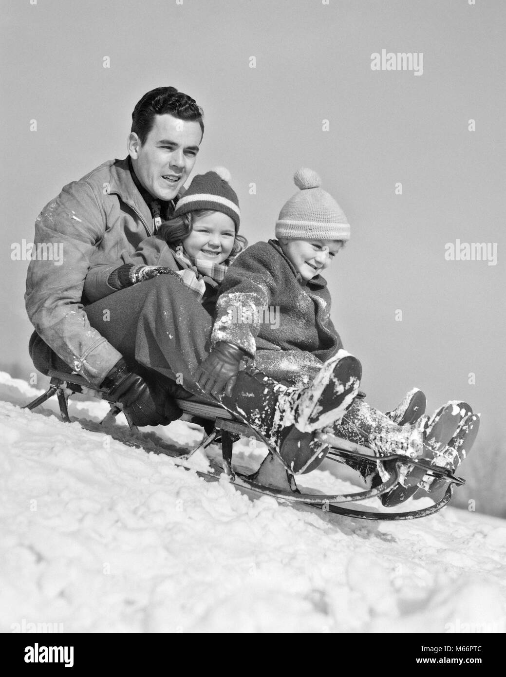 1930s 1940s FATHER TWO CHILDREN ON SLED IN SNOW GOING DOWN HILL - w4217 HAR001 HARS OLD TIME BROTHER OLD FASHION - Stock Image