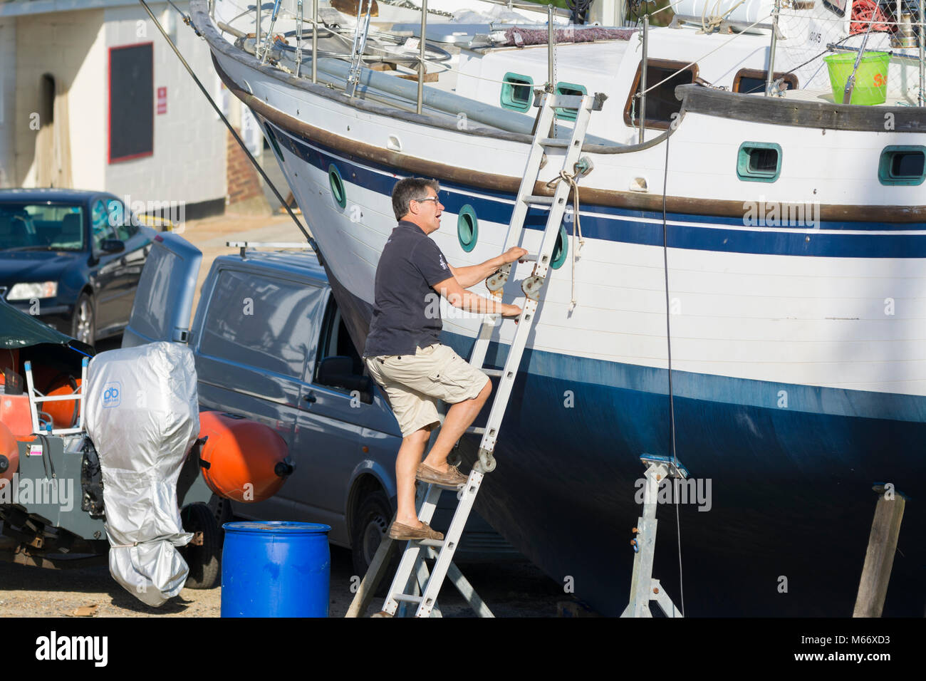 Man climbing up a ladder onto a boat on stands in dry dock, out of water in a boat yard. Boat maintenance. - Stock Image
