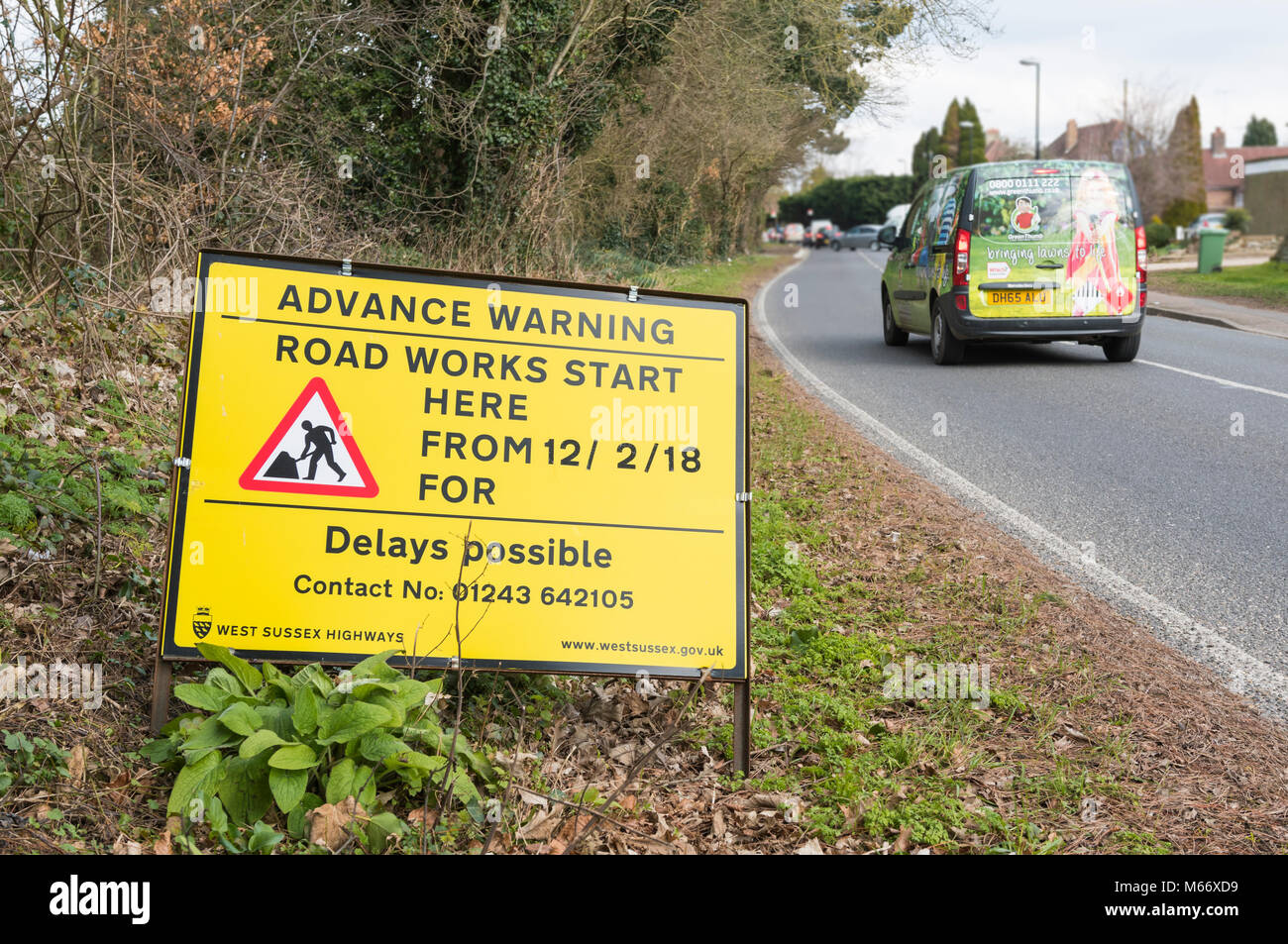 Yellow advance warning roadside sign to warn of delays due to road works starting in Angmering, West Sussex, England, - Stock Image