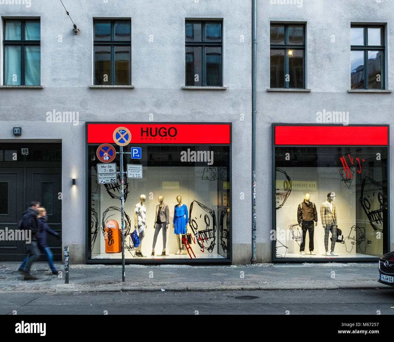 Berlin,Mitte, Hugo Boss Men's designer clothing store, Display window with mannequins showing male & female - Stock Image